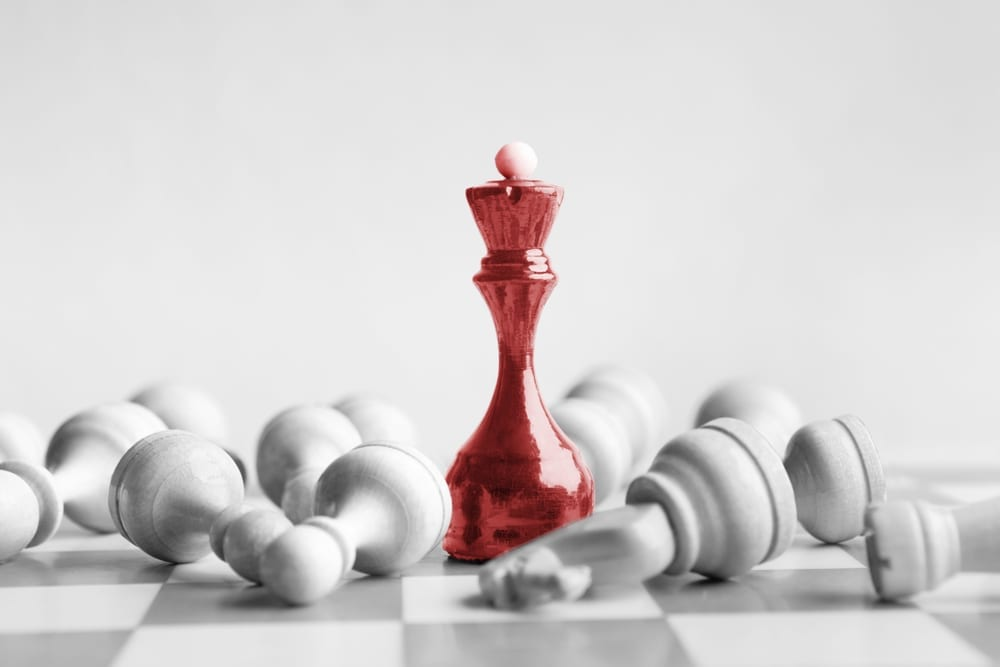 red chess queen stands with toppled white chess pieces all around