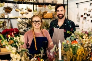 photo of a florist shop with a man and a woman in aprons smiling