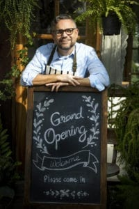 man standing behind a chalkboard sign with the words Grand Opening written on it