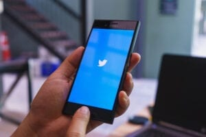hands holding phone with twitter logo showing